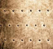 picture of stelles  - Closeup of grunge gold brown metal plate with rivets and screws as background or texture - JPG