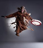 pic of shaman  - Studio shot of angry shaman posing in jump, on gray background