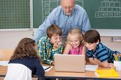 picture of senior class  - Young school kids in class grouped around a laptop computer on a desk with a male teacher leaning over watching them work - JPG