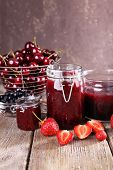 stock photo of jar jelly  - Berries jam in glass jar on table - JPG