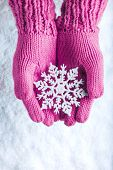 stock photo of wonderful  - Woman hands in light pink knitted mittens with sparkling wonderful snowflake on a white snow background - JPG