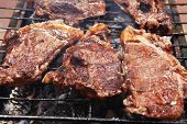 stock photo of charcoal  - fresh hot bbq grill red beef meat steak ready on grid over charcoal with marks - JPG