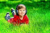 pic of 7-year-old  - 7 years old boy lying on a grass and listening to music in headphones - JPG