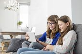 picture of three sisters  - Happy sisters using digital tablet on sofa at home - JPG