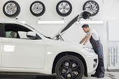 stock photo of car repair shop  - Full length side view of male mechanic examining car engine in repair shop - JPG
