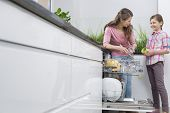 picture of dishwasher  - Happy mother and daughter placing glasses in dishwasher at kitchen - JPG