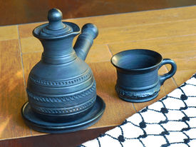 stock photo of loamy  - Ceramic coffeepot and cup on a table - JPG