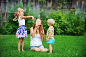 stock photo of blowers  - mother and her children play with bubble blower on green lawn - JPG
