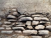 pic of cobblestone  - Cutting of an old road with cracked asphalt and a gully in the center of cobblestones - JPG