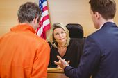 stock photo of court room  - Lawyer speaking about the criminal in orange jumpsuit in the court room - JPG