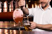 pic of pores  - Cropped image of smiley bartender poring beer to the mug - JPG