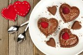 picture of chocolate spoon  - Heart shaped chocolate dessert cups with pudding and raspberries on plate with wood background - JPG