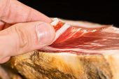 pic of shoulder-blade  - Caucasian man left hand over serrano ham with slice - JPG