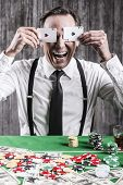 stock photo of suspenders  - Happy senior man in shirt and suspenders sitting at the poker table and covering his eyes with cards - JPG