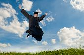 stock photo of graduation hat  - Young smiley graduate student in gown jumping over blue sky - JPG
