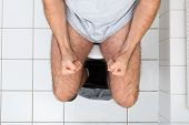 stock photo of toilet  - High Angle View Of A Man Clenching His Fist Sitting On Toilet Bowl - JPG