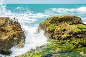 stock photo of slam  - Turquoise rolling wave slamming on the rocks of the coastline - JPG
