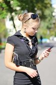pic of lurex  - portrait of a beautiful cute girl in a black dress with phone in hand - JPG