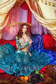 picture of harem  - Oriental beauty sitting in a tent and holding a sword on her head - JPG