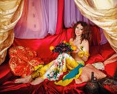 picture of harem  - Young oriental beauty sitting in a tent and holding a dish with ripe fruit - JPG