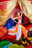 picture of harem  - Sexy oriental beauty in a tent and sword in hand abuts her hip - JPG