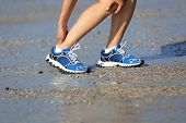 stock photo of ankle shoes  - young woman runner hold her twisted ankle - JPG