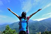 pic of open arms  - young cheering woman hiker open arms at mountain peak - JPG