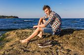 foto of nearly nude  - Attractive young fashion sexy man sitting on a rock near the sea water with shoes beside him - JPG