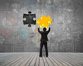 pic of insert  - Businessman inserting gold jigsaw puzzle piece into the dark hole with business concept doodles wall background - JPG