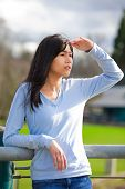 pic of biracial  - Young biracial teen girl standing leaning against railing at park shading eyes to look off to side - JPG
