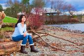 picture of biracial  - Young biracial teen girl in blue shirt and jeans sitting on large log on rocky beach by lake - JPG