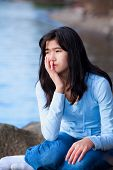 picture of biracial  - Sad biracial teen girl in blue shirt and jeans sitting on rocks along lake shore lonely expression - JPG