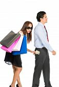 image of unawares  - A shopaholic greedy Asian wife with sunglasses department store bags steals money unnoticed from the pants pocket of her husband as he walks away - JPG