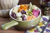 stock photo of glass heart  - Colorful Italian pasta dish served with artichoke hearts and kalamata olives in a ceramic bowl accompanied by a glass of Chianti wine for dinner or lunch - JPG