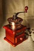 pic of wooden box from coffee mill  - Coffee bean grinder is on the burlap sack background - JPG