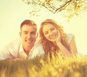 picture of grass  - Happy Smiling Couple Together Relaxing on Grass in a Park - JPG