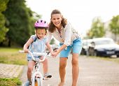 picture of car ride  - A laughing smiling mother pushes her daughter forward on a warm summer - JPG