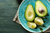 stock photo of avocado  - Sliced avocado and lemon lime on wooden background - JPG