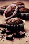 image of chocolate muffin  - chocolate muffins with chocolate slices on wooden background  - JPG