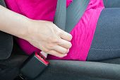 picture of seatbelt  - A girl wearing a pink shirt buckling a seatbelt - JPG
