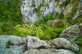 stock photo of ravines  - Mountain landscape with deep ravine on springtime - JPG