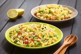 image of cucumbers  - Vegetarian couscous salad made with bell pepper tomato cucumber red onion and sweet corn kernels served on plates cutlery and lemon on the side - JPG