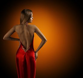 stock photo of red back  - Woman Naked Back Womanly Fashion Model Posing Sexy Red Dress Elegant Girl Rear View Looking Side over Shoulder - JPG