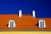 image of gabled dormer window  - orange roof with two windows and chimneys against blue sky - JPG