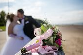 Постер, плакат: Newly married couple and wedding bouquet in the foreground Wedding bouquet with the wedding couple