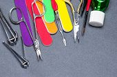 Various Manicure Tools On Gray Textured Background poster
