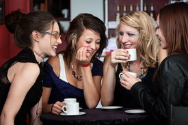 picture of foursome  - A foursome of pretty girls laughing in a cafe - JPG
