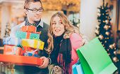 Couple, man and women, shopping  Christmas presents and bags in mall poster