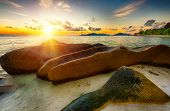 Beautifully shaped granite boulders and a dramatic sunset  at Anse Source dArgent beach, La Digue i poster