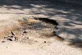 Постер, плакат: Bad Road Pits Potholes And Puddles After Rain On Paved Road Background Is An Old Road With Cracke